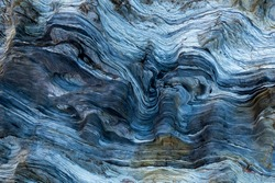 Marks of sea water and wind erosion on a blue toned rock  from light to dark.The natural process of erosion created smooth and fluid lines, holes and sharp layers. It looks like it was carved.