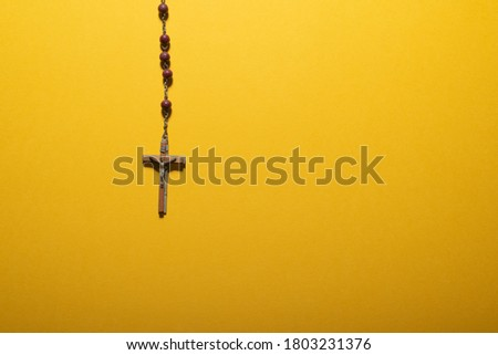 Maroon beads rosary with wooden crucifix over plain yellow. Copy space available for adding text such as masses or church activities. Communion invitation background