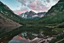 Maroon Bells in Aspen Colorado at Sunset. Beautiful maroon colors and pink clouds reflecting off glassy water. Reflection of mountain tops on water framed between cliffs and trees