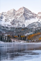 Maroon Bells morning sunrise peak vertical view in Aspen, Colorado rocky mountain and autumn yellow foliage and winter snow