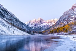 Maroon Bells morning sunrise reflection with sunlight on peak in Aspen, Colorado rocky mountain and autumn yellow foliage view and winter snow frozen lake