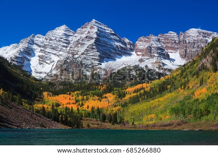 Maroon Bells on a peaceful and beautiful Autumn day. With Snow covered mountains.