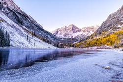 Maroon Bells sunrise reflection with pink sunlight on peak in Aspen, Colorado rocky mountain and autumn yellow foliage view and winter snow frozen lake