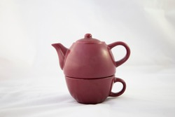 Maroon ceramic teapot on white background. Individual view. Trim. It is divided into two parts because it is an individual teapot that has the glass for tea at the bottom. Two handles are seen
