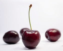 maroon cherry in the foreground and three similar maroon cherries in the background on a white background
