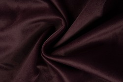 Maroon fabric texture - top view and close-up of a piece of crushed and twisted red satin