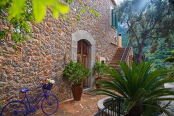 Maroon,grey stone house with stairs in  Deià,small coastal village in the Serra de Tramuntana,Mallorca,Spain with lot of greenery,palm,violet bycicle,mountains, mist,light ray,haze,plants,perspective