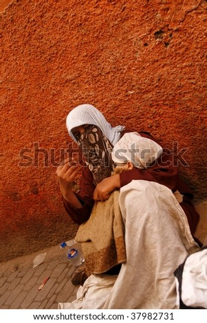 MARRAKECH, MOROCCO-APRIL 24:A mother with baby beg on the street April 24, 2009 in Marrakech.A 2009 study shows 4 million Moroccans live below the national poverty line, 3 million are from rural areas - stock photo