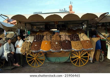 MARRAKESH – CIRCA FEB 2009: Two street vendors stand by dried fruit stall at Djemaa el Fna square in Marrakesh, Morocco circa February 2009. The market is frequently visited by locals and tourists. - stock photo