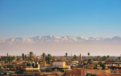 Marrakesh city skyline in Morocco with snowy Atlas mountains in the background