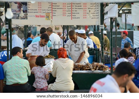 MARRAKESH - JULY 09: Unidentified people sells food in Jemaa el Fna Square at sunset, July 09, 2013 in a Marrakesh, Morocco. The square is part of the UNESCO World Heritage