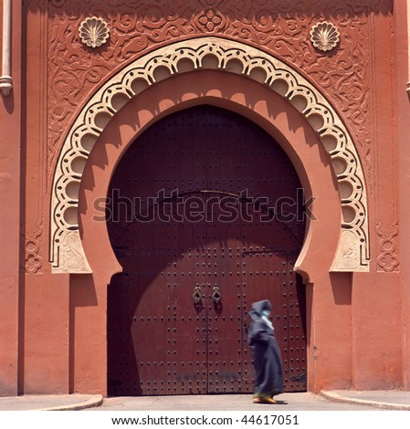 Marrakesh medina decorated gate.Lady is not recognizable because of total veil. - stock photo