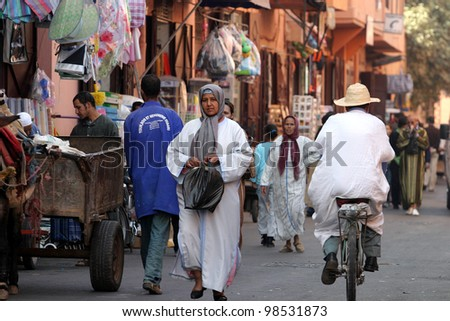 MARRAKESH, MOROCCO - OCTOBER 28: People walking in bazaar at famous Marrakesh square Djemaa el Fna on October 28, 2007 in Marrakesh, Morocco. The square is part of the UNESCO World Heritage. - stock photo