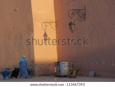 MARRAKESH, MOROCCO - OCTOBER 27: Unidentified woman walking at the sunset near the Koutoubia mosque in the city center on October 27, 2008 in Marrakesh, Morocco. The souk is part of UNESCO WH.