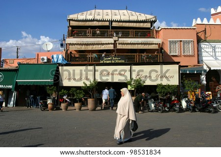 MARRAKESH, MOROCCO - OCTOBER 28: Woman walking at famous Marrakesh square Djemaa el Fna on October 28, 2007 in Marrakesh, Morocco. The square is part of the UNESCO World Heritage.