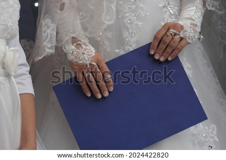Marriage contract in the hands of bride at a traditional Jewish wedding. in Hebrew 'ktuba' means Hebrew religions marriage agreement. Ketubah - a prenuptial agreement in the Jewish religious tradition Foto stock ©