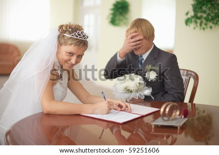 Marriage registration. The bride is happy. The groom in grief.