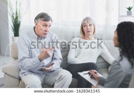 Marriage Therapist. Angry elderly husband complaining about his wife during therapy session, sitting on couch Stock photo ©