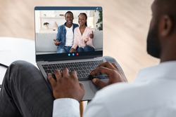 Marriage Therapy Online. Black counselor speaking with happy couple via video call on laptop computer, over shoulder view, selective focus