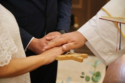 Marriage, vow on the cross, newlyweds and a Catholic priest