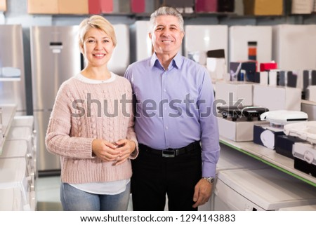 Married adults are visiting shop of household appliances for buying goods for kitchen and house.  #1294143883
