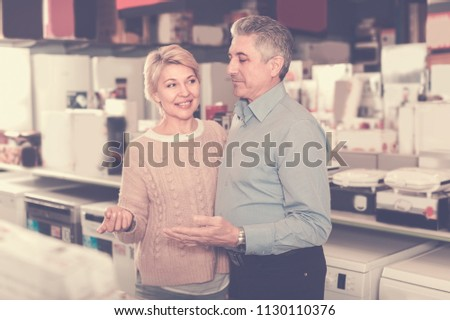Married adults are visiting shop of household appliances for survey of goods for kitchen and house. #1130110376