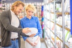 Married cheerful couple checking date of manufacture on circle of cheese while walking along supermarket diary shelves together.