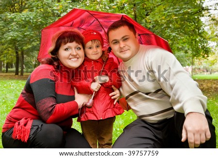 Married couple and  little girl on an umbrella in park