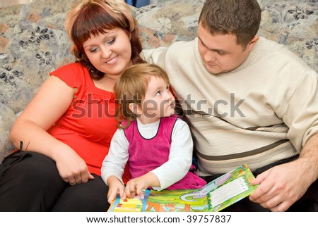 Married couple and  little girl read  book in a cozy room