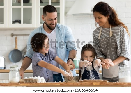Married couple and their little kids preparing pie or dessert in kitchen at home. Parents teaching children to cook domestic food, siblings helping to mom and dad, education, hobby and pastime concept