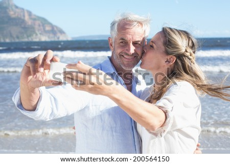 Married couple at the beach together taking a selfie on a sunny day