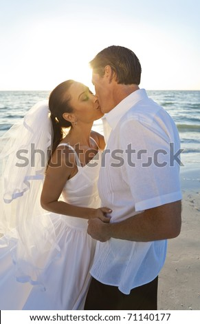 Married couple, bride and groom, kissing at sunset on a beautiful tropical beach wedding
