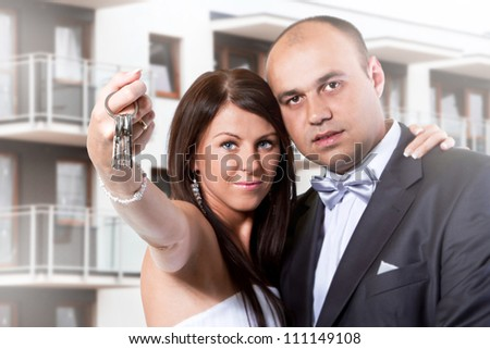 Married couple holding keys to new home