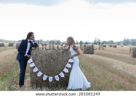 Married couple standing with the elbows on a hay bale that is written Just married.