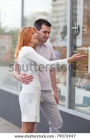 married couple to stand at a shop show-window. The woman shows on the pleasant thing.