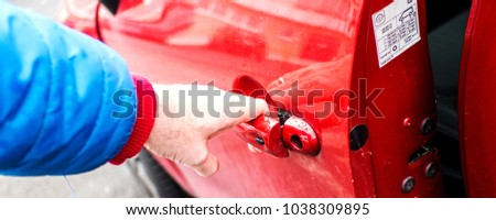 married man is opening front door of his red dirty car without car key