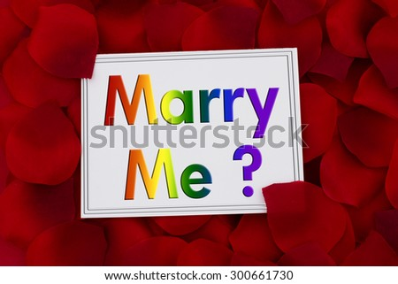Marry Me Card, A white card with text Marry Me in LGBT pride colors and a red rose pedal backgrounds