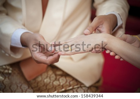 Marry me. Groom put a ring on finger of his lovely wife