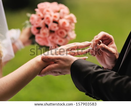 Marry me. Groom put a ring on finger of his lovely wife. Wedding couple together.