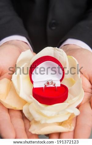 Marry me. Groom\'s hand offering wedding ring