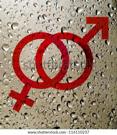 Mars Venus or Male Female symbol on surface covered with rain drops. Birth Control.