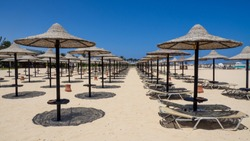 Marsa Matruh, Egypt. August 1, 2019. Rows of umbrellas made of straw and sunbeds. Sandy beach. Relaxing context. Fabulous holidays. Mediterranean Sea. North Africa