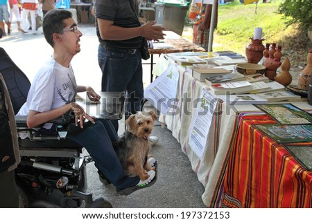 MARSEILLE, FRANCE - AUGUST 26: Photo of a young man in a wheelchair with his pet. Marseille Festival Association on August 26, 2012 in Park Borelli, Marseille, France