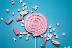Marshmallows and lolly pop on the blue background.