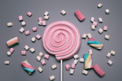Marshmallows and lolly pop on the grey background.