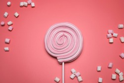 Marshmallows and lolly pop on the pink background.