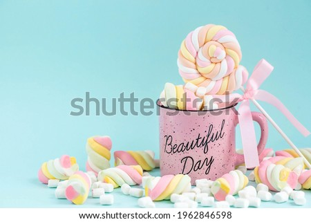 Marshmallows. Chewy candy close-up on a turquoise background. Dessert of sweet food in a cup with hot chocolate. Pastel colors. Copy of the text space. Stock photo ©