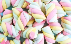Marshmallows. Chewy candy close-up on a turquoise background. The dessert of sweet food. Pastel colors. Copy of the text space.