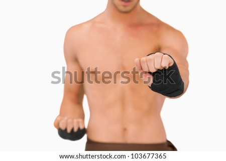 Martial arts fighter doing his exercises against a white background
