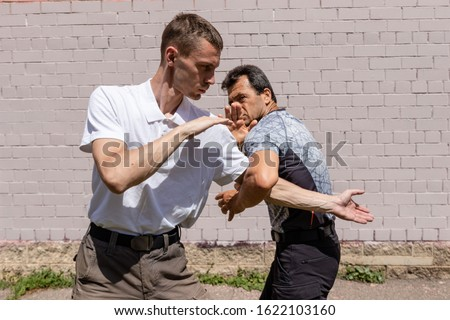 Martial arts instructors demonstrate self-defense techniques of Krav Maga. he defender dodges the attack, holding the attacker by the elbow.